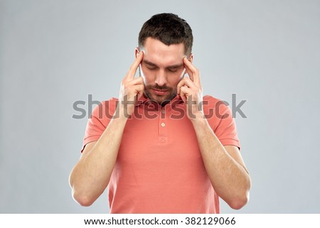 people, crisis, emotions and stress concept - man suffering from head ache or thinking over gray background - stock photo