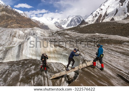 People Crossing Glacier Crevasse on Wood Shaky Footbridge Group of Mountain Climbers with High Altitude Boots and Clothing Crossing Ice Section During Ascent of Alpine Expedition in Asia Mountain Area - stock photo