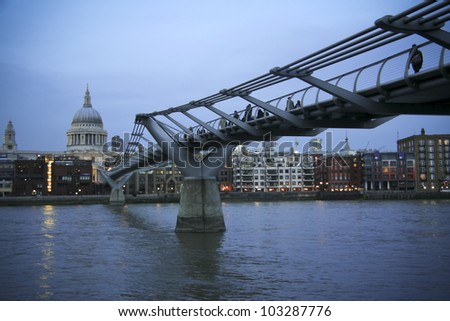 people crossing the millennium bridge across the river thames in london uk at night - stock photo