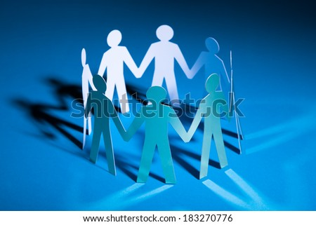 People Cut Out Of Paper Holding Hand Together - stock photo