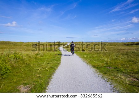 People cycling on a bike path through the dune landscape of Frisian Island Amsland, the Netherlands - stock photo