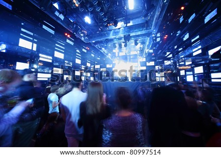 People dancing at concert in nightclub, light show and loud music - stock photo