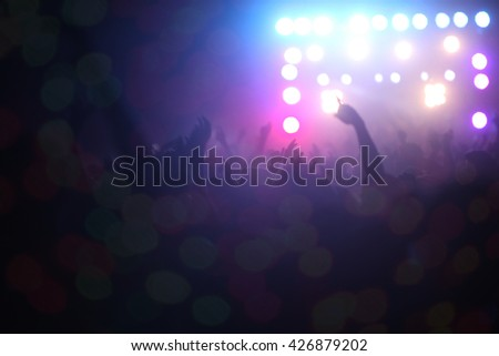 People dancing in front of a stage during a musical concert in India.