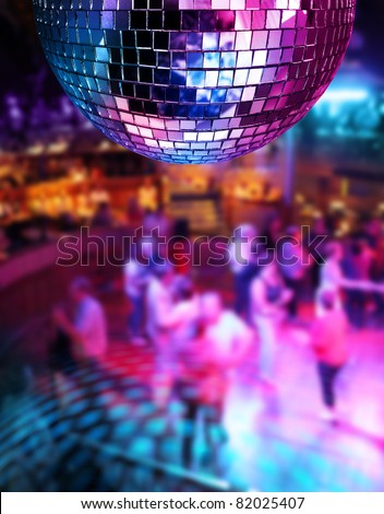 People dancing under colorful lights of disco mirror ball - stock photo