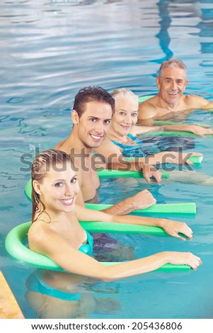People doing aqua fitness as back training in a swimming pool - stock photo