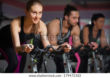 People doing indoor biking in a fitness club - stock photo