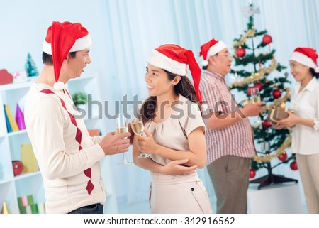 People drinking champagne and chatting at the Christmas party - stock photo