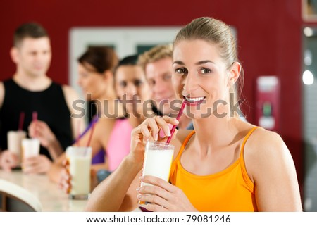 People drinking protein shake after workout in gym or fitness club