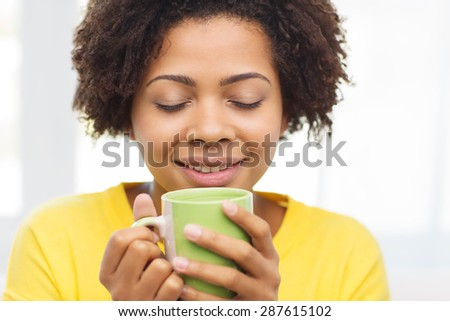 people, drinks and leisure concept - happy african american woman drinking tea from cup or mug at home - stock photo