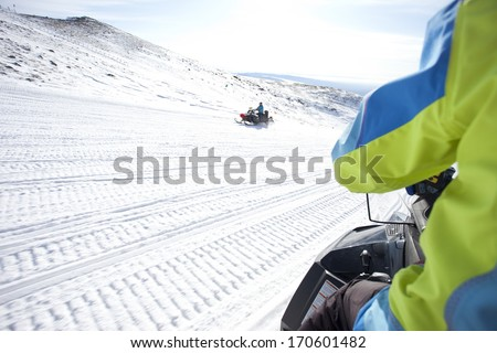 people driving  snowmobile in winter mountain ,china - stock photo