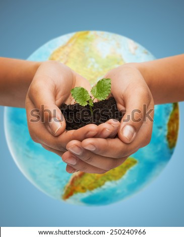 people, ecology, environment, agriculture and food concept - close up of woman hand with green sprout over earth globe over blue background - stock photo