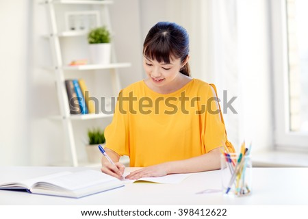people, education, high school and learning concept - happy asian young woman student with book and notepad writing at home - stock photo