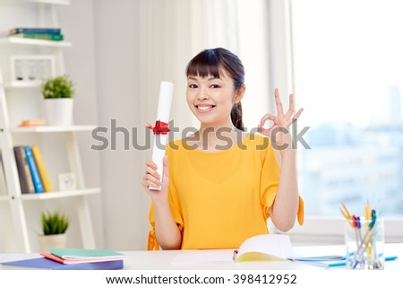 people, education, school, graduation and learning concept - happy asian young woman student with diploma scroll at home showing ok hand sign - stock photo