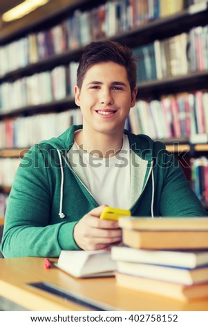 people, education, technology and school concept - male student with smartphone and books in library - stock photo
