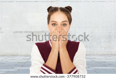 people, emotion, expression and teens concept - scared or confused teenage girl over gray urban street background - stock photo