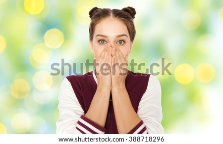 people, emotion, expression and teens concept - scared or confused teenage girl over green summer holidays lights background - stock photo