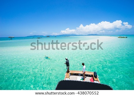 People enjoying coral cay and clear tropical water with a boat, Yaeyama Islands, Okinawa, Japan - stock photo