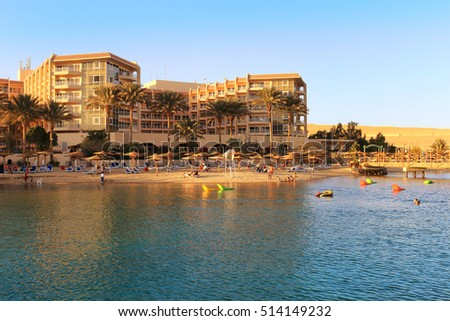 People enjoying the beach area with sun shades and lounging chairs at a resort on the Red Sea in Hurghada, Egypt