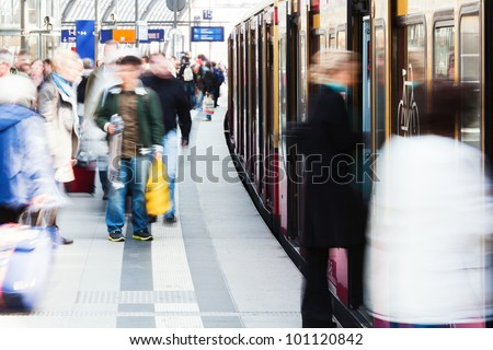 people enter a train at the railway station - stock photo