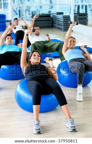 People exercising at the gym with weights and pilates ball - stock photo