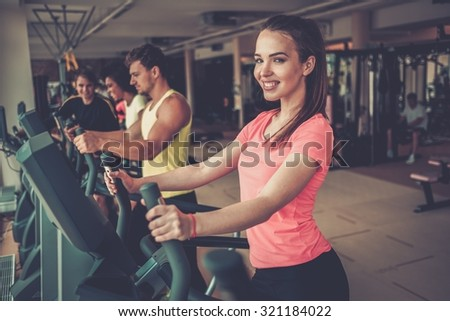 People exercising on a cardio training machines in a gym - stock photo