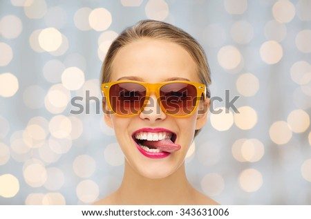 people, expression, joy and fashion concept - smiling young woman in sunglasses with pink lipstick on lips showing tongue over holidays lights background - stock photo