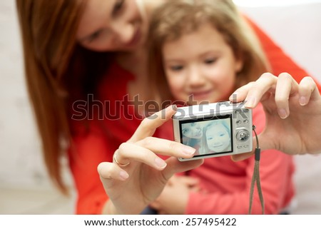 people, family and technology concept - close up of happy mother and little daughter with camera taking selfie - stock photo