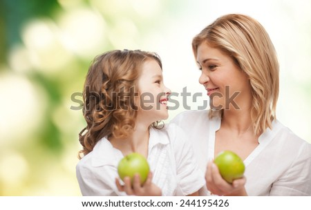 people, family, healthy eating and parenting concept - happy mother and daughter with apples over green background - stock photo