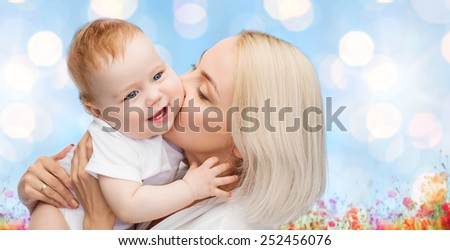 people, family, motherhood and children concept - happy mother hugging adorable baby over blue lights and poppy field background - stock photo