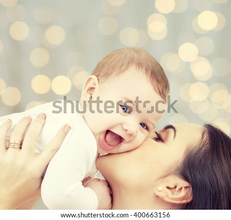 people, family, motherhood and children concept - happy mother hugging adorable baby over holidays lights background - stock photo