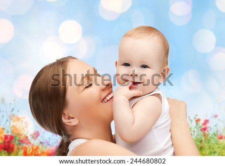 people, family, motherhood and children concept - happy mother hugging adorable baby with finger in his mouth over blue lights and poppy field background - stock photo