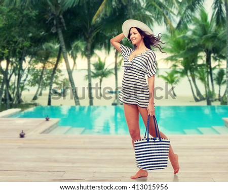 people, fashion, summer and beach concept - happy young woman in summer clothes and sun hat with bag over swimming pool at beach resort - stock photo