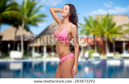 people, fashion, summer vacation and travel concept - happy young woman posing in pink bikini swimsuit over hotel resort with swimming pool, bungalow and palm trees background - stock photo