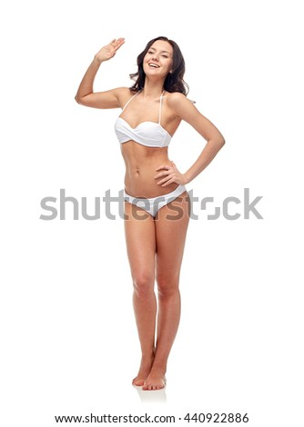 people, fashion, swimwear, summer and beach concept - happy young woman in white bikini swimsuit waving hand - stock photo