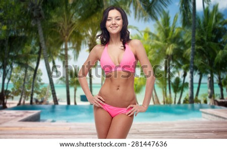 people, fashion, swimwear, summer and travel concept - happy young woman posing in pink bikini swimsuit over tropical beach with swimming pool background - stock photo