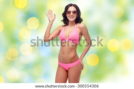 people, fashion, swimwear, summer beach and gesture concept - happy young woman in sunglasses and pink swimsuit waving hand over green holidays lights background - stock photo