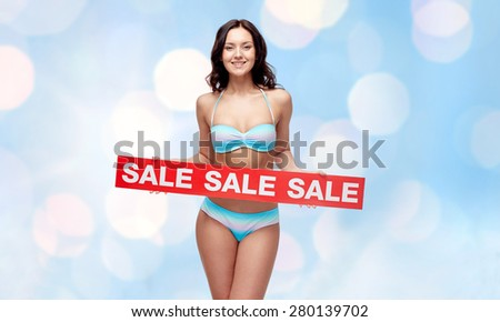 people, fashion, swimwear, summer shopping and beach concept - happy young woman in bikini swimsuit with red sale sign over blue holidays lights background - stock photo