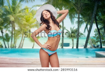 people, fashion, travel, tourism and summer concept - happy young woman in bikini swimsuit and sun hat over swimming pool and beach with palm trees background - stock photo
