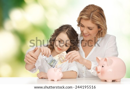people, finances, family budget and savings concept - happy mother and daughter with piggy banks and paper money over green background - stock photo