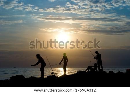 People fish. The sea, evening, the beautiful sky. - stock photo