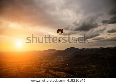 People fly a paraglider on a background of beautiful scenery. - stock photo