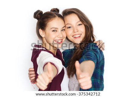 people, friends, teens and friendship concept - happy smiling pretty teenage girls hugging and showing thumbs up - stock photo