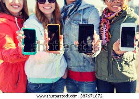 people, friendship, cloud computing, advertising and technology concept - close up of happy teenage friends showing blank smartphone screens outdoors - stock photo