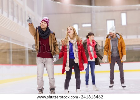 people, friendship, sport, gesture and leisure concept - happy friends pointing finger on skating rink - stock photo