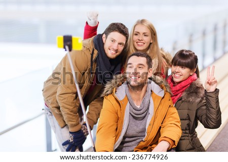 people, friendship, technology and leisure concept - happy friends taking picture with smartphone selfie stick on skating rink - stock photo
