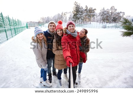 people, friendship, technology and leisure concept - happy friends taking picture with smartphone selfie stick on ice skating rink outdoors - stock photo