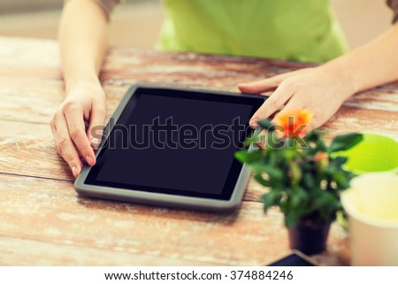 people, gardening, flowers and profession concept - close up of woman or gardener with tablet pc computer black blank screen at home - stock photo
