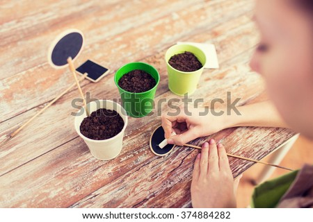 people, gardening, seeding and profession concept - close up of woman writing name on garden sign over pots with soil and seeds - stock photo
