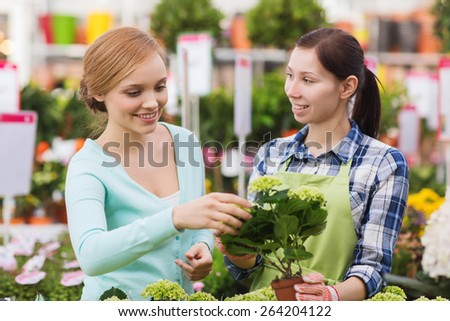 people, gardening, shopping, sale and consumerism concept - happy gardener helping woman with choosing flowers in greenhouse - stock photo