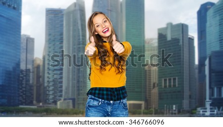 people, gesture, travel, tourism and fashion concept - happy young woman or teen girl in casual clothes showing thumbs up over city buildings background - stock photo
